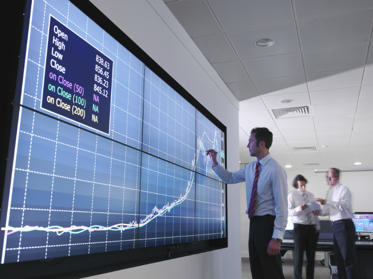 Man in front of board showing share performance